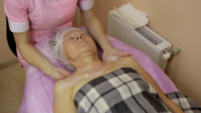 Relaxed elderly woman getting spa massage video