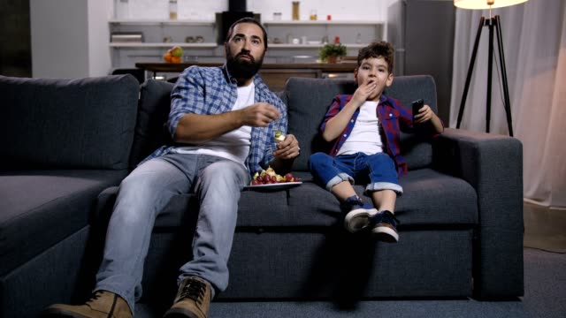 Relaxed father and son watching movie on tv Relaxed bearded single father and cute mixed race son with remote control watching movie on tv and eating delicious fruit kebabs while enjoying freetime together on sofa in domestic room. family watching tv stock videos & royalty-free footage