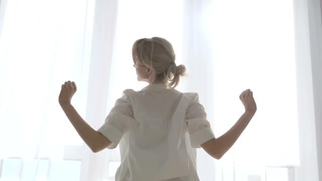 vídeos y material grabado en eventos de stock de mujer femenina relajada que se extiende cerca de la ventana, ritual de la mañana saludable, estilo de vida - espalda humana