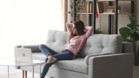 zrelaksowana dziewczyna odpoczywająca na kanapie ciesz się bezstresowym dniem - relaks filmów i materiałów b-roll