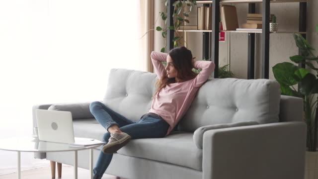 entspannte mädchen ruhen sitzen auf dem sofa genießen stressfreien tag - atemübung stock-videos und b-roll-filmmaterial