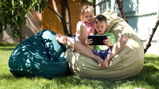 タブレットと一緒に時間を過ごすリラックスした子供 - 兄弟姉妹点の映像素材/bロール