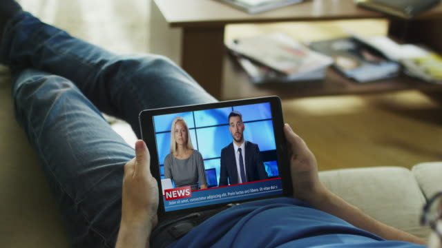 relaxed man lying on his couch watches news broadcast on his tablet computer. - democrazia video stock e b–roll