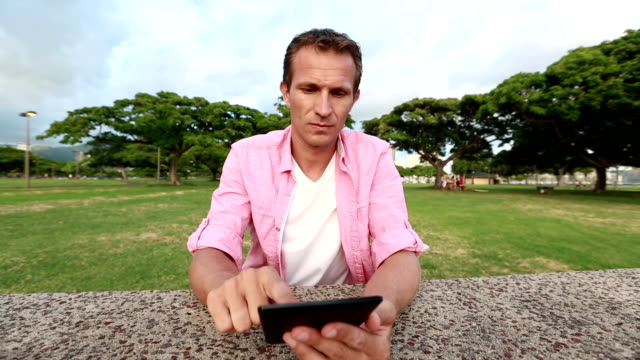 stockvideo's en b-roll-footage met ontspannen man lezing ebook in the park - e learning