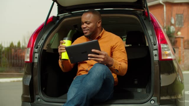 Relaxed man using tablet pc while sitting in car trunk