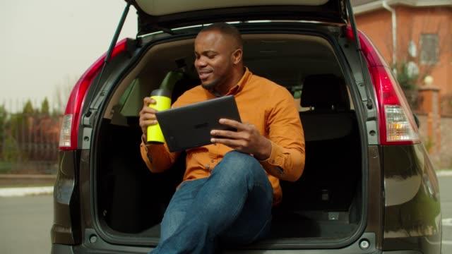車のトランクに座っている間タブレットpcを使用してリラックスした男 - environmentalism点の映像素材/bロール