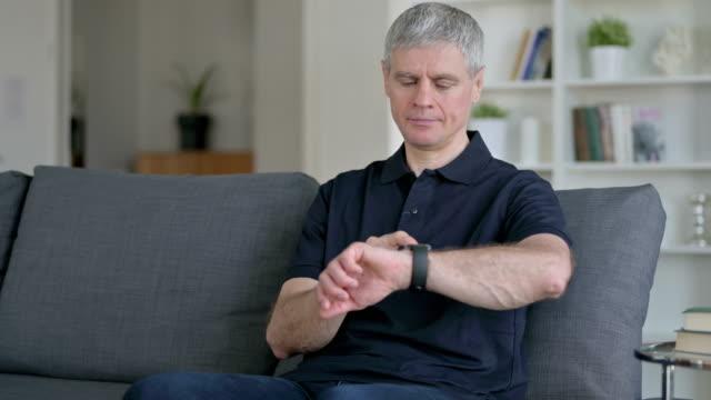 relaxed middle aged businessman using smartwatch at home - staw człowieka filmów i materiałów b-roll