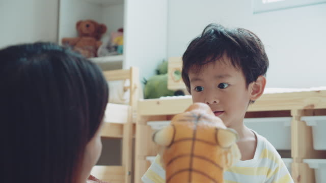 avslappnad föräldraskap. asiatiska mor och son leker leksaker - parent talking to child bildbanksvideor och videomaterial från bakom kulisserna