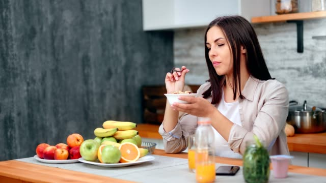 vídeos de stock e filmes b-roll de relaxed smiling morning female having breakfast in kitchen at home - granola