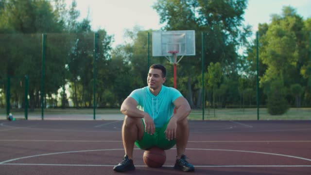 Relaxed streetball player sitting on basketball