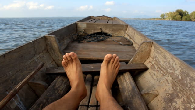 Relaxed tourist moving feet playfully during a boat ride video
