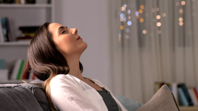 Relaxed woman breathing at home in the night
