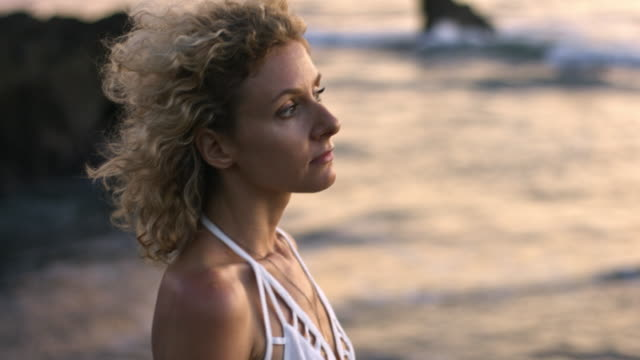 stockvideo's en b-roll-footage met ontspannen vrouw genieten van de avond op het strand - blond curly hair