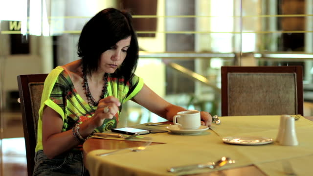 relaxed woman in holidays using smartphone sitting drinking coffee at the bar video