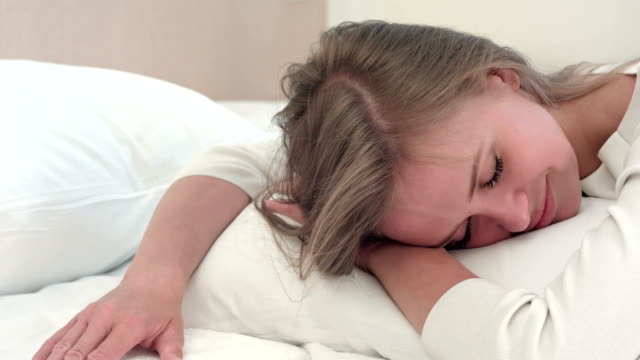 Relaxed young blonde girl sleeping on white bed at home or in hotel room Relaxed young blonde girl sleeping on white bed at home or in hotel room. Close up. Professional shot in 4K resolution. 073. You can use it e.g. in your commercial video, business, hotel, presentation, broadcast video. resting stock videos & royalty-free footage