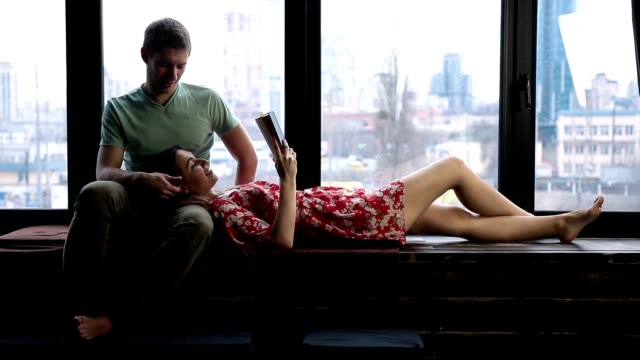 Relaxed young couple reading book together at home video
