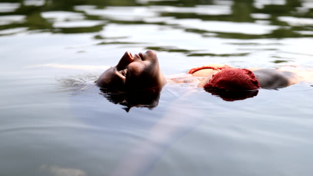 vídeos de stock, filmes e b-roll de fêmea jovem relaxada flutuando no lago - flutuando na água