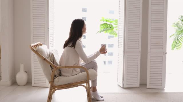 vídeos de stock, filmes e b-roll de jovem relaxada bebendo chá olhando pela janela no apartamento - tea drinks