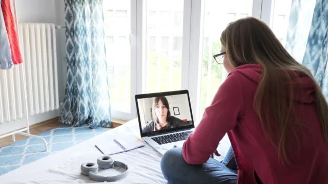 vídeos y material grabado en eventos de stock de mujer joven relajada teniendo videollamada en el ordenador portátil durante la cuarentena - navegar por la red