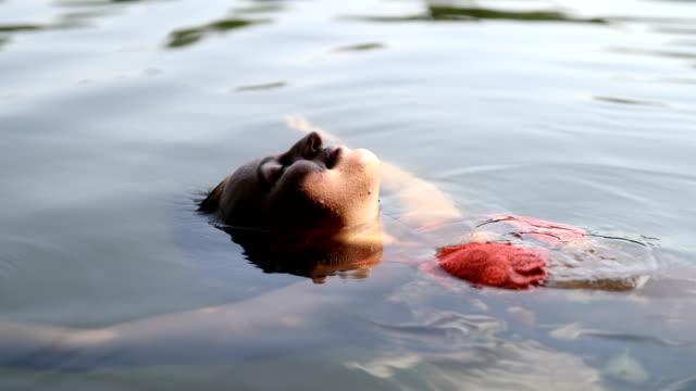 Relaxed young woman in bikini floating on lake