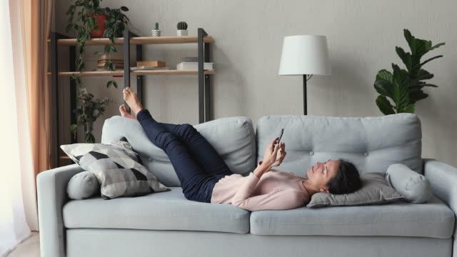 giovane donna rilassata sdraiata sul divano usando lo smartphone - divano video stock e b–roll