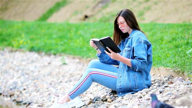 vidéos et rushes de livre de lecture détendue jeune femme - allongé sur le dos