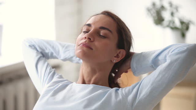 Relaxed young woman with happy face breathing fresh air chilling Relaxed young woman with happy face eyes closed breathing fresh air chilling with hands behind head, calm smiling girl dreaming enjoying peace of mind meditating lounging on stress free day concept mindfulness stock videos & royalty-free footage