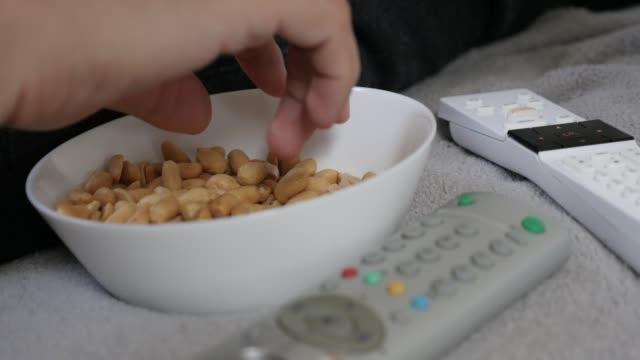 テレビを見てピーナッツを食べて自宅でリラックス 4k - おやつ点の映像素材/bロール