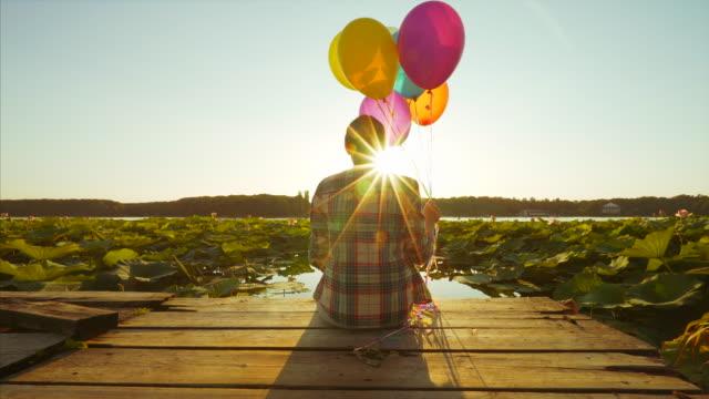 vídeos de stock e filmes b-roll de relaxing at sunset. - mulher balões