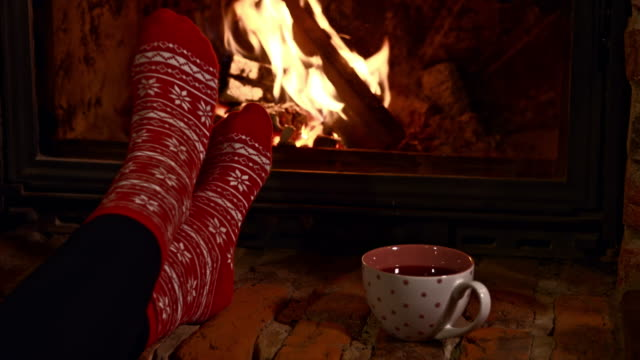 DS Relaxing by the fireplace Dolly shot of a young woman relaxing by the fireplace at home. View of a cup of tea, woman's feet in winter socks and the fireplace. Also available in 4K resolution. chalet stock videos & royalty-free footage