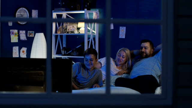 Relaxing family watching TV on bed together View through window of adult parents and teen son chilling on bed at night time and watching TV while laughing family watching tv stock videos & royalty-free footage
