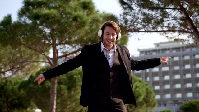Relaxing from business problems Young businessman is dancing while listening favorite song on headphones in park. bluetooth stock videos & royalty-free footage