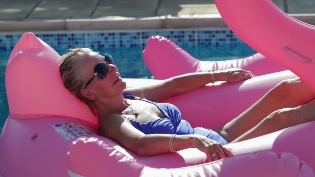 Relaxing in an Inflatable on Holiday Close-up view of a senior woman relaxing in a flamingo shaped inflatable. She is looking at the camera and laughing. swimwear stock videos & royalty-free footage