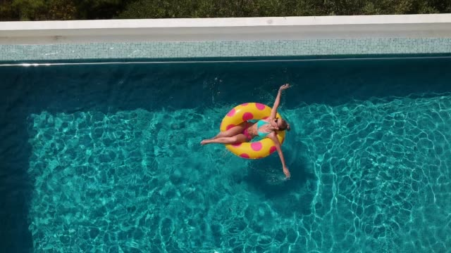 Relaxing in the pool Aerial view video of a woman relaxing on a inflatable ring and floating in the pool holiday stock videos & royalty-free footage