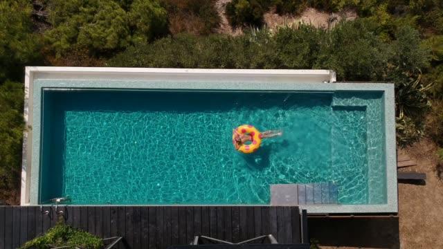 stockvideo's en b-roll-footage met ontspannen in het zwembad - opblaasband