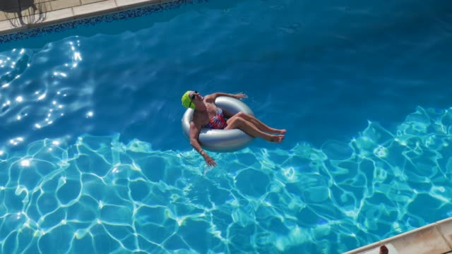 Relaxing on Holiday High angle view of a senior woman relaxing in an inflatable on the the water in the swimming pool. floating on water stock videos & royalty-free footage