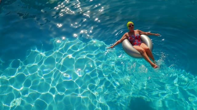 Relaxing on Holiday High angle view of a senior woman relaxing in an inflatable on the the water in the swimming pool. sunbathing stock videos & royalty-free footage