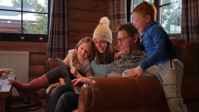 stockvideo's en b-roll-footage met ontspannen op de bank met zijn gezin - christmas cabin