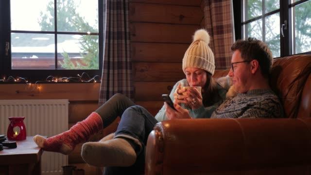 relaxing on the sofa with his wife - zima filmów i materiałów b-roll