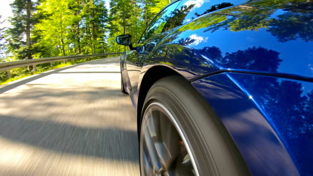 Relaxing scenic car drive on an empty winding mountain road on a beautiful sunny day Driving an elegant and luxurious blue sports car on an empty winding mountain road through picturesque scenery on a beautiful sunny day sports car stock videos & royalty-free footage