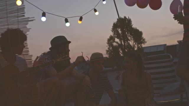 vidéos et rushes de se détendre entre amis à la fête sur le toit - man drinking terrace