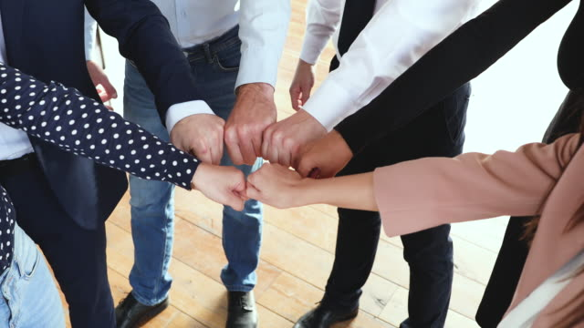 reliable business team people join fists together in circle, closeup - fedeltà video stock e b–roll