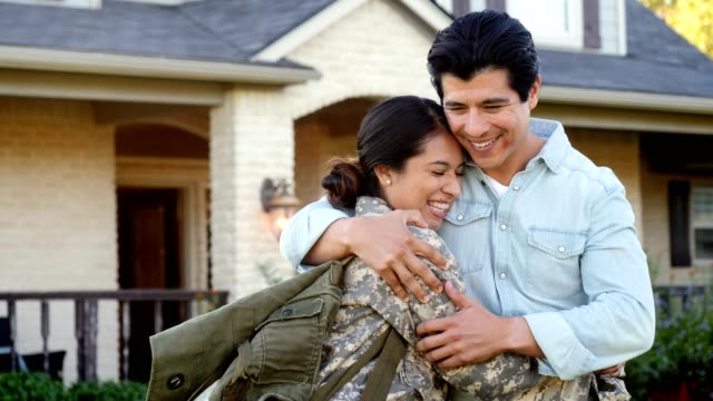Relieved female soldier returns home from deployment Excited mid adult female soldier hugs her husband upon her return from military assignment. They smile at one another. veteran stock videos & royalty-free footage