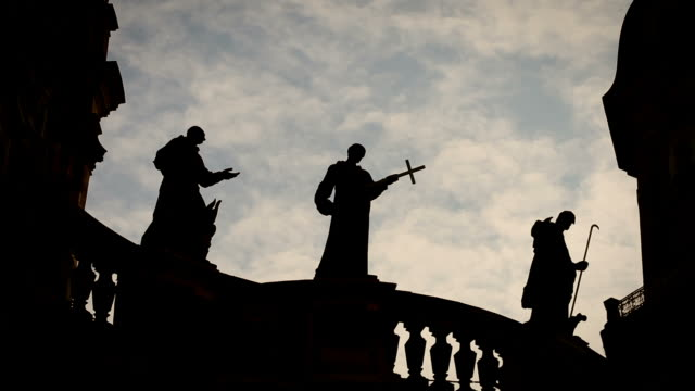 Religion / Priest Statues on a church - moving clouds