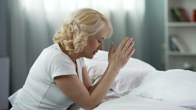 Religious mature woman sitting near bed with clasped hands and praying, religion video