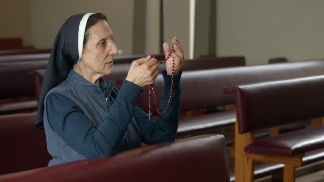 vídeos y material grabado en eventos de stock de hermana religiosa de rodillas y sosteniendo el rosario. - misa