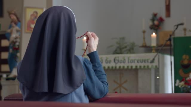 Hermana religiosa arrodillarse en pew y sosteniendo el Rosario. - vídeo