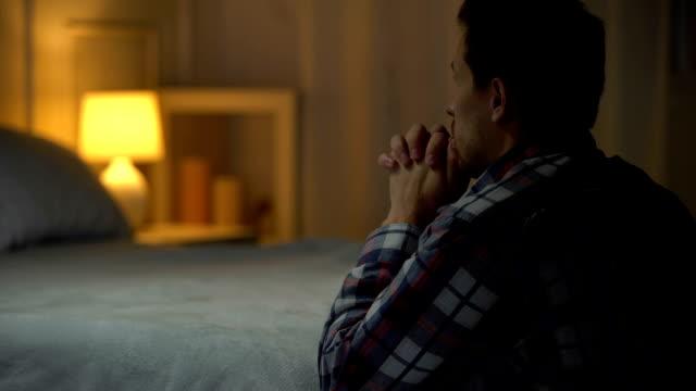religijny młody człowiek modlący się wieczorem w pobliżu łóżka, wiara w boga, chrześcijaństwo - modlić się filmów i materiałów b-roll