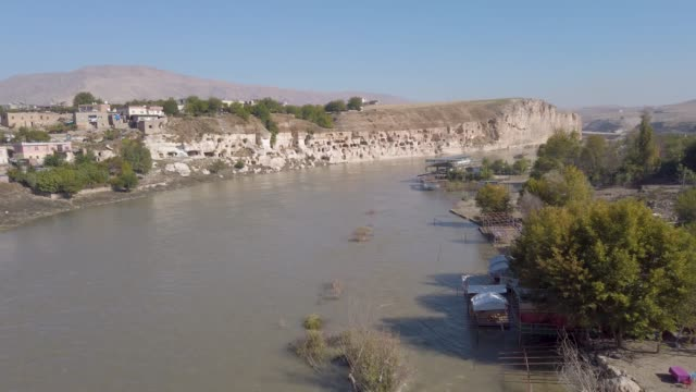 Remains of the ancient village of Hasankeyf on the River Tigris Hasankeyf, Turkey - October 2019: Remains of the town of Hasankeyf on the River Tigris, famous with stone caves after it is evacuated. The town will be sunk under water of ilisu dam mardin stock videos & royalty-free footage