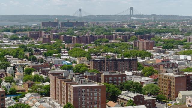 vidéos et rushes de vue à distance du pont verrazano-narrows sur le quartier résidentiel de brooklyn, new york. drone vidéo avec le mouvement de la caméra panoramique. - hlm